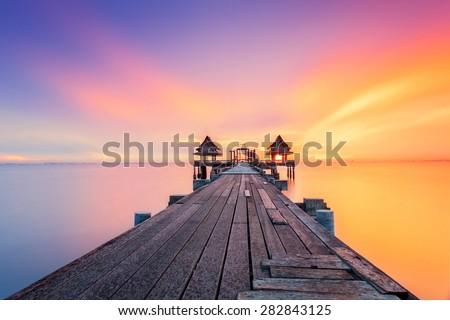 Wood bridge at sunset light in sea - stock photo