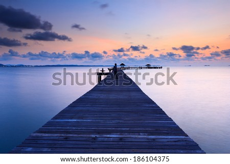 wood bridge to the sea at sunrise.