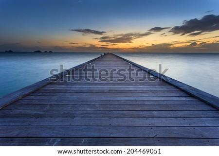 Wood bridge to the sea at sunset beach in Koh Samui, Thailand - stock photo