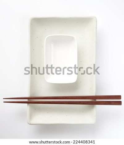 Wood brown chopstick on ceramic white plate - stock photo