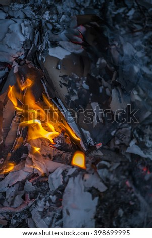 Wood burning and flames rising up from a back-yard fire pit - stock photo