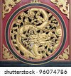 Wood Carving Chinese Dragon on Outside Temple Door with Bats Motif - stock photo