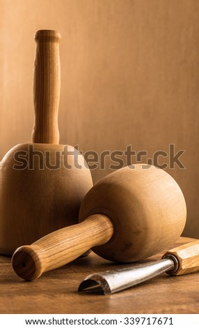 Wood carving chisel and mallets on table against textured wallpaper - stock photo