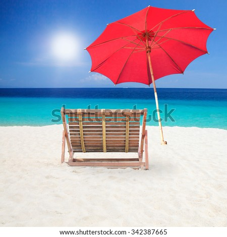 Wood chairs and red umbrella on the beach. - stock photo