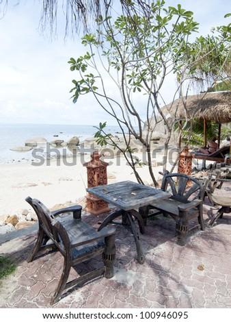 wood chairs on tropical beach - stock photo