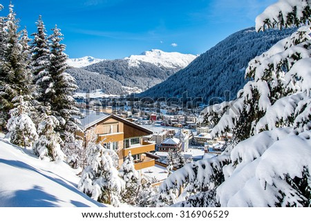 Wood chalet over snowy mountains in  Davos, Switzerland. - stock photo