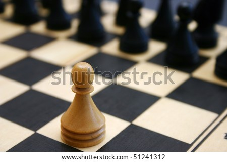 Wood chess game shows white brave pawn challenge stronger enemy.