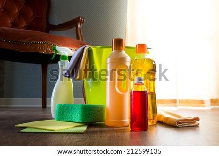 Wood cleaners with bucket, gloves and sponge on living room hardwood floor. - stock photo