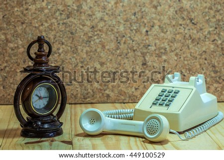 Wood clock an Telephone analog on wood table and wood background. - stock photo