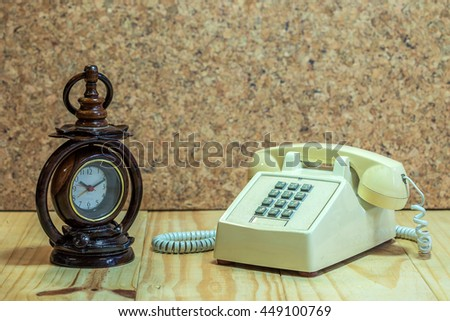 Wood clock and telephone analog on wood table and wood background. - stock photo