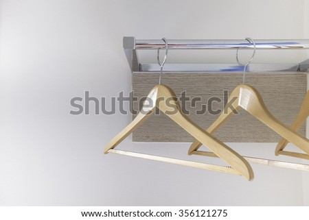 wood cloth hanger on metal rail and wood panel on white wall background - stock photo