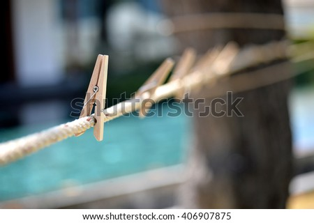 Wood clothespin hanging on rope outdoor, selective focus - stock photo