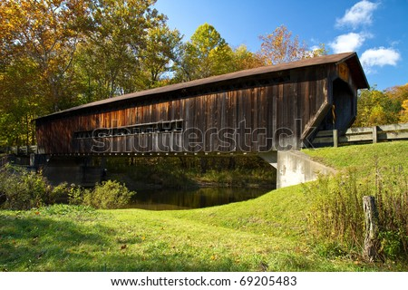 Wood covered bridge in Ashtabula County, Ohio on a fall day - stock photo