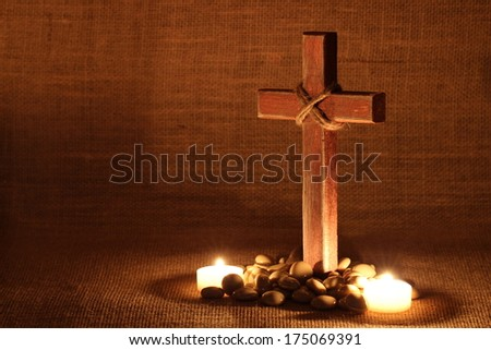 Wood cross by candlelight and stones by burlap background - stock photo