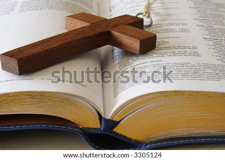 Wood cross on a page of the bible - stock photo