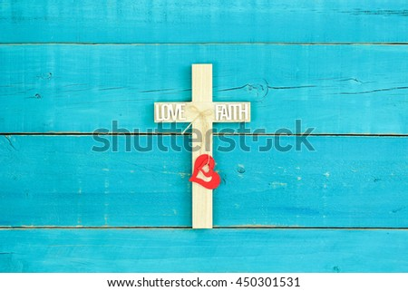 Wood cross with red hearts, FAITH and LOVE on antique rustic teal blue wooden background - stock photo