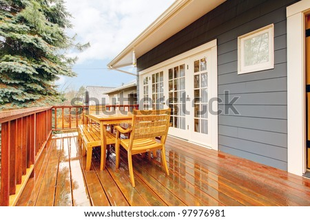 Wood deck during the rain with table and chairs and grey house.