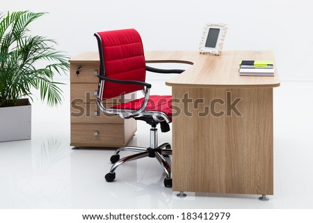 wood desk and red armchair on a white wall - stock photo