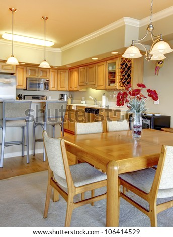 Wood dining room table near kitchen in luxury apartment. - stock photo