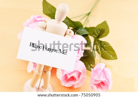 Wood Doll Holding Up an Apology Note - stock photo