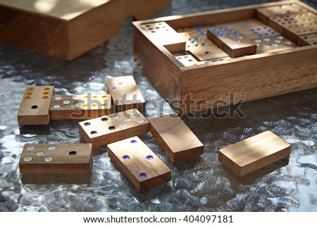 Wood domino game on glass table, daylight - stock photo