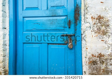 Wood door in blue color is locked with padlock, texture and background - stock photo