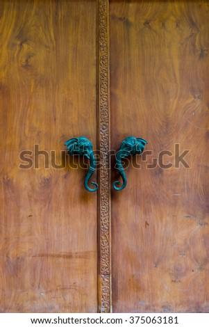 Wood door with elephant head door handle - stock photo