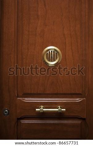 wood door with golden peephole - stock photo