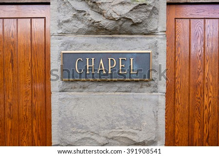 Wood doors and a sign that says chapel at a very old historic church in an urban setting.