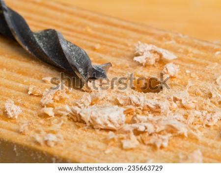 Wood drill on wooden plank with wood chips, selective focus on drill tip - home improvement, diy or woodworking concept - stock photo