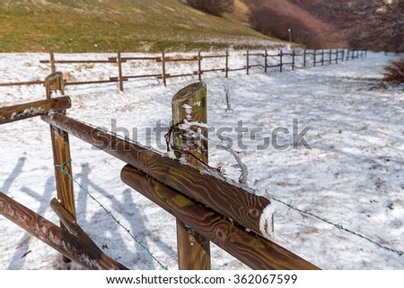 wood fence, barbed wire and snow