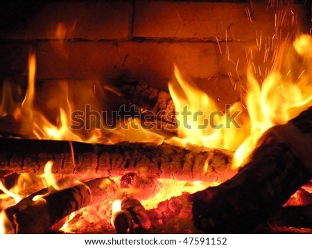 Wood fire in the fireplace, sparks fly on both sides