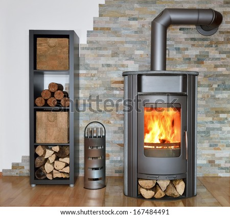 wood fired stove with fire-wood, fire-irons, and briquettes from bark - stock photo