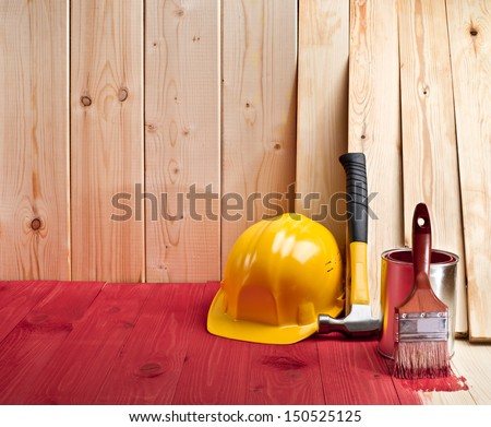 wood floor and wall with a brush, paint, hammer and yellow helmet - stock photo