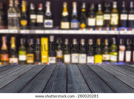 wood floor and wine Liquor bottle on shelf - Blurred background - stock photo