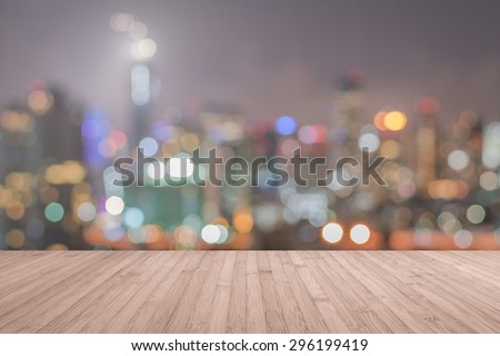 Wood floor in light red brown color tone with blurred abstract background of Bangkok night lights downtown city view with bokeh with light flare : Wooden table with blur background of cityscape  - stock photo