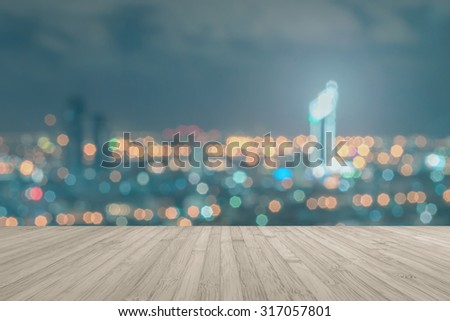 Wood floor in light sepia brown color tone with blurred abstract background of Bangkok city night lights rooftop view with bokeh and light flare: Wooden table with blur background of urban cityscape  - stock photo