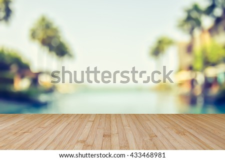Wood floor natural wooden deck texture in light yellow beige brown color tone w/ blur abstract background blurry view tropical resort hotel swimming pool seaside ocean view coconut palm tree blue sky - stock photo