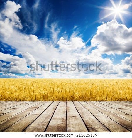 Wood floor over yellow wheat field under nice sunset cloud sky background - stock photo