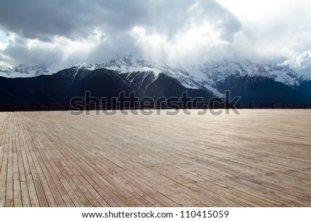 Wood floor with a background of mountains and clouds - stock photo