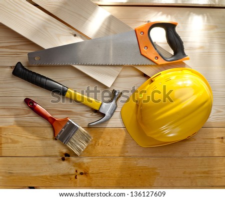 wood floor with a brush, saw, hammer and helmet