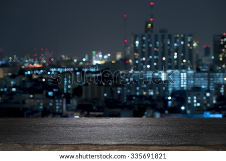 Wood floor with blurred abstract background of city night lights downtown city view : Wooden table with blur background of cityscape - stock photo