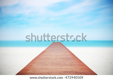 Wood floor with white blue surfing wave background. Blue cool water and sky bright with ray light. Nature wallpaper blur of sea daytime. Focus to wooden in the foreground. Timber pattern texture stage