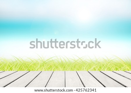 Wood floor with white blue surfing wave background. Blue water and sky bright and green grass. Nature wallpaper blur of sea daytime. Focus to wooden in the foreground. Timber pattern texture stage. - stock photo