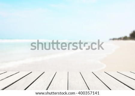 Wood floor with white blue surfing wave background. Blue water and sky bright. Nature wallpaper blur of sea daytime. Focus to wooden in the foreground. Timber pattern texture stage. - stock photo