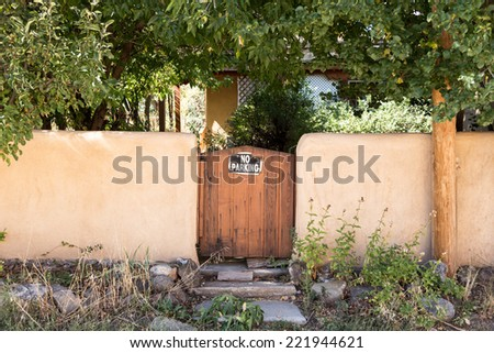 Wood gate in stucco wall no parking sign
