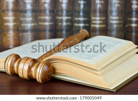 Wood gavel and old yellowed book on the background of shelves of old books - stock photo