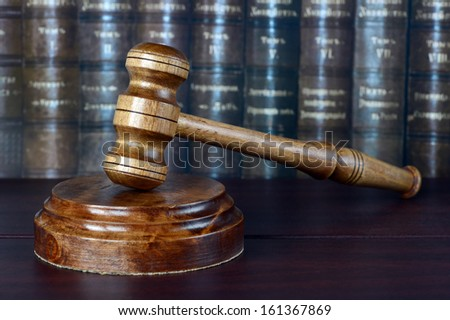 Wood gavel and soundblock on the background of shelves of old books - stock photo