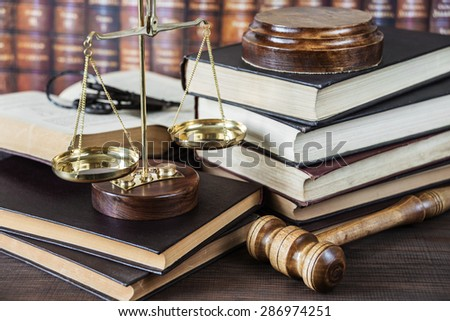 Wood gavel, bunch of keys, scales and stack of old books against the background of a row of antique books bound in leather - stock photo