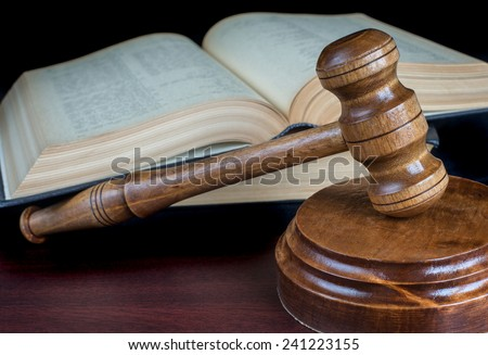 Wood gavel, soundblock and stack of thick old books on a black background - stock photo